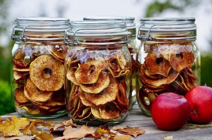 Torkade äppelringar i glasburkar med höstlöv och äppleringar bredvid