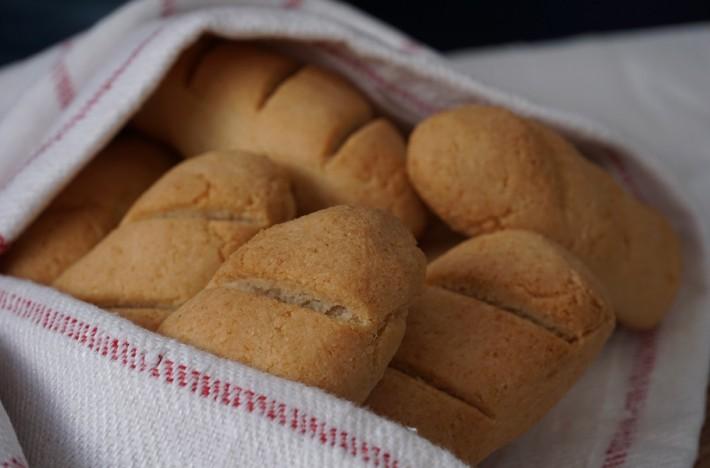 Brytbröd i en brödkorg med kökshandduk runt