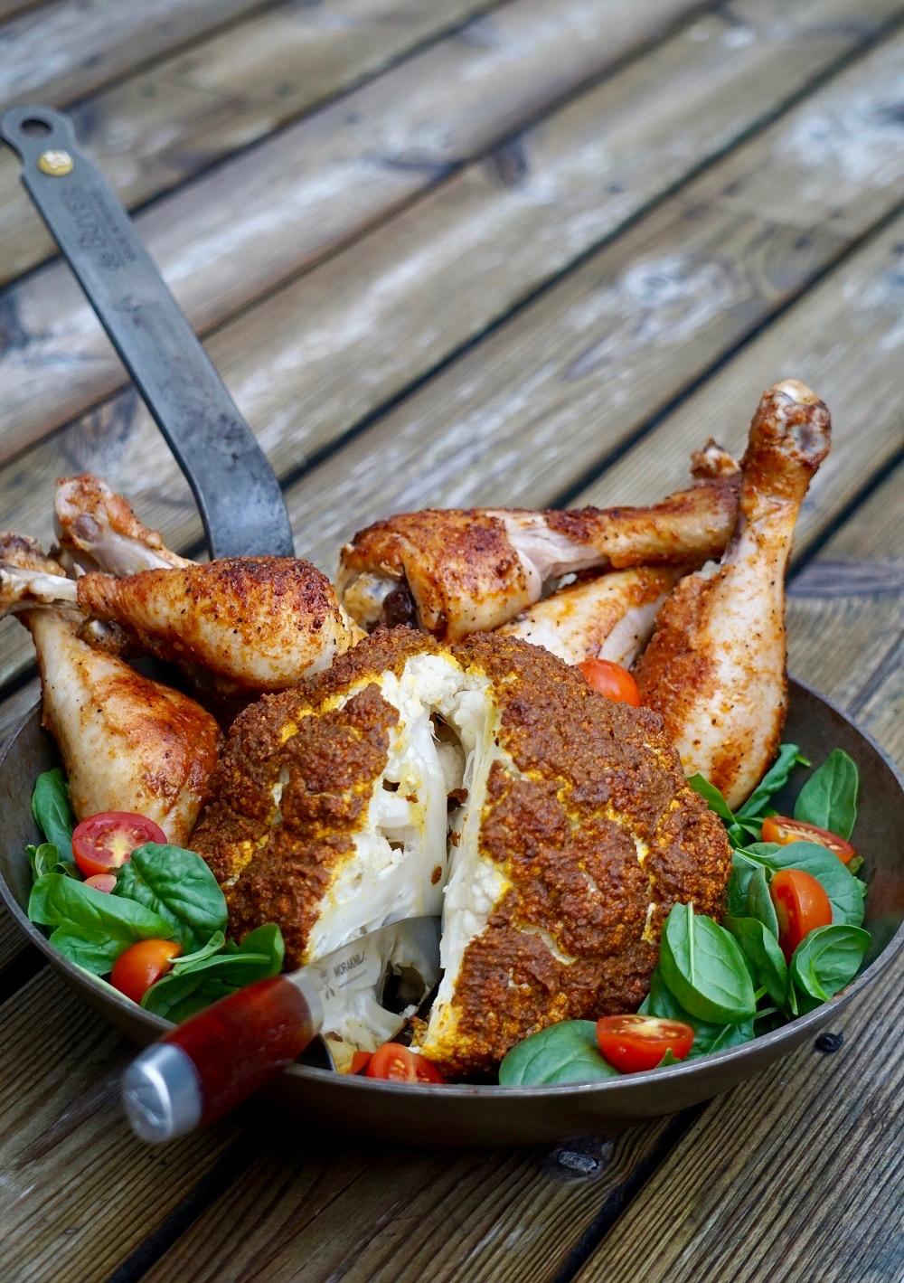 Helrostad blomkål och grillade kycklingben i en stekpanna