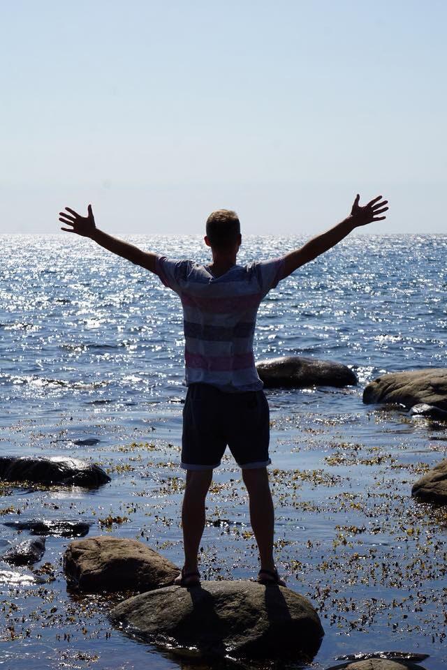 En person står på en sten i strandkanten, representerar frisk mage med probiotika trots IBS