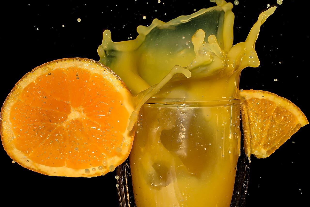 apelsiner som krockar med ett glas juice fyllt med c-vitamin