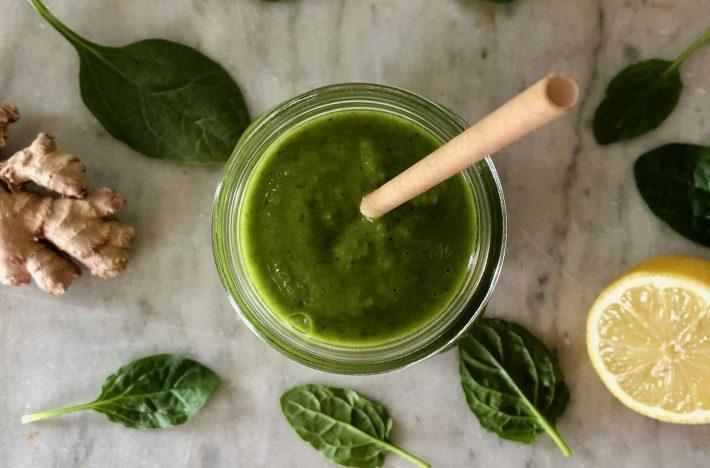 Grön hälsosmootie i glas med sugrör