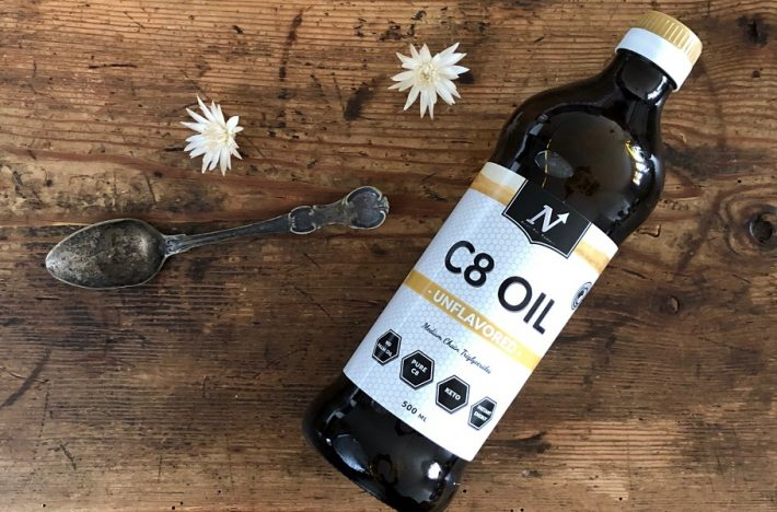 En flaska med MCT-olja av märket Nyttoteket C8 Oil tillsammans med en matsked olja