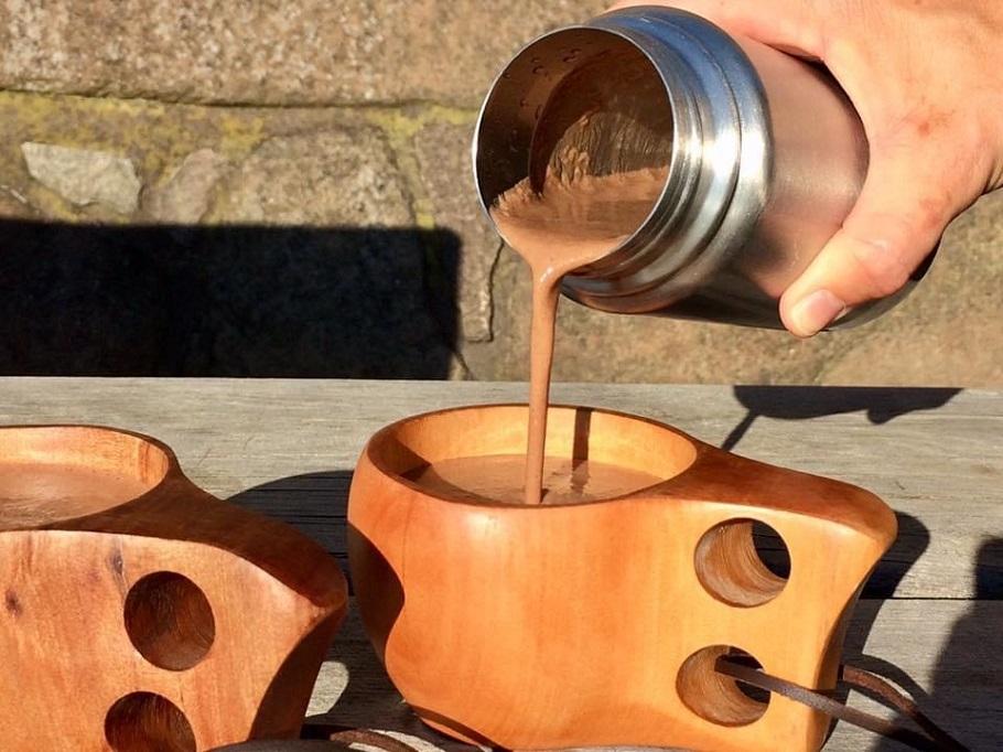 Häller upp varm choklad från en termos ner i en träkåsa