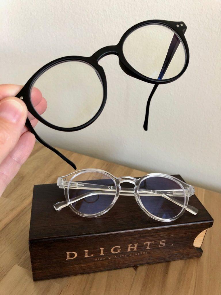 Två par blåljusblockerande glasögon från DLIGHTS tillsammans med en träask