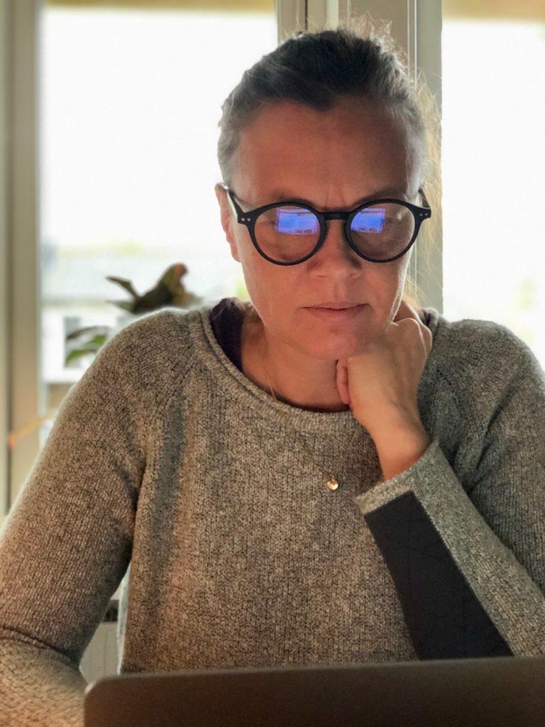 Sitter framför datorn med blåljusblockerande glasögon