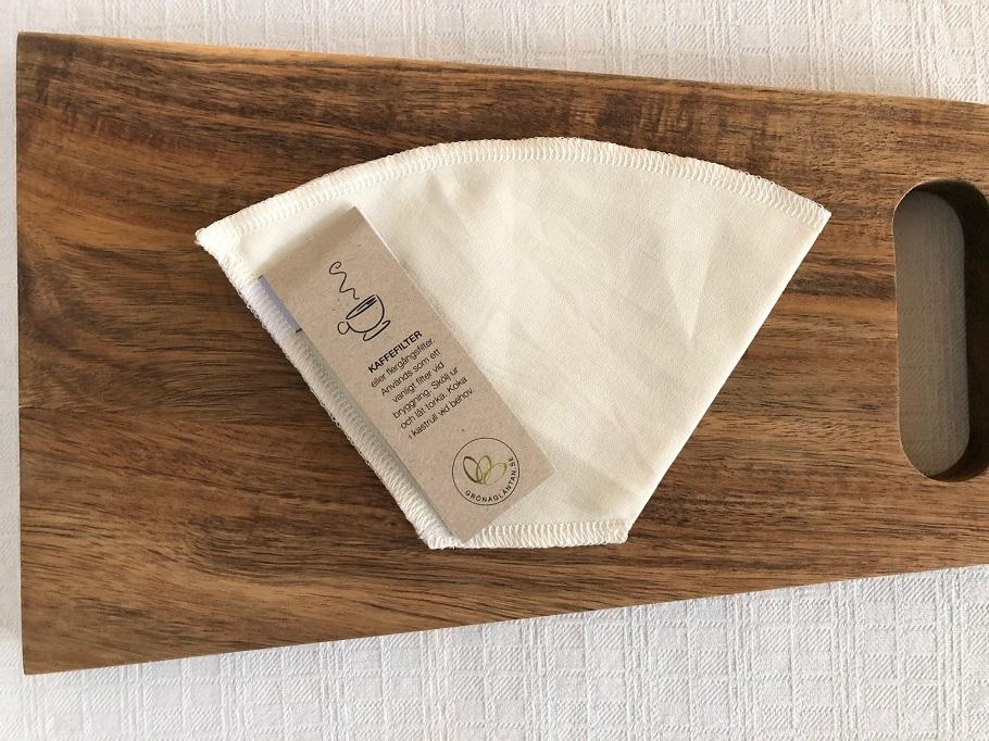 Ekologiskt kaffefilter i bomull på en skärbräda