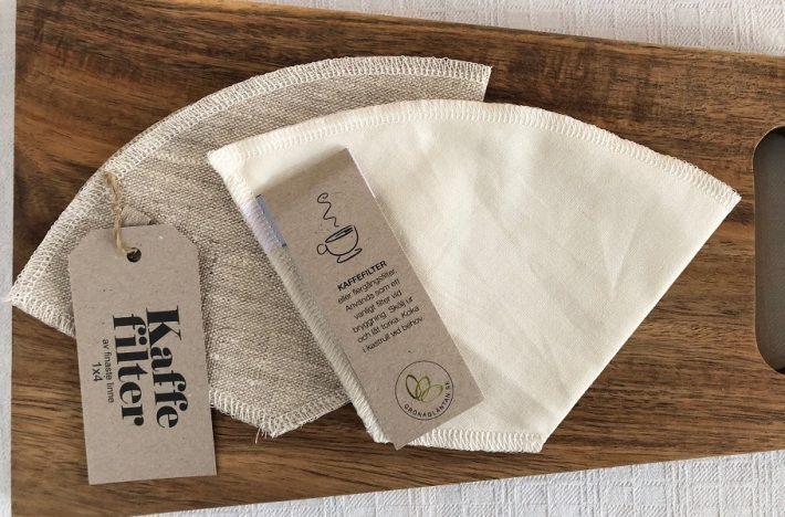Två olika återanvändbara kaffefilter, ett i bomull och ett i linne, på en skärbräda.